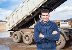 Smiling young worker and tip truck Royalty Free Stock Image