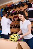 Smiling young workers arranging bicycle helmets on shelves. In bike shop royalty free stock photos