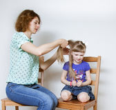 Smiling ypung mother braiding hair her little daughter Stock Photography