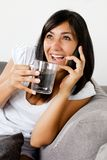 Smiling yung woman talking on the phone while sitting on couch drinking a coffee Royalty Free Stock Photo