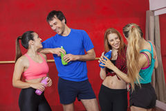 Smiling Zumba Dancers Holding Water Bottles In Gym. Smiling male and female Zumba dancers holding water bottles in gym Royalty Free Stock Photography