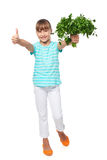 Smilinglittle girl showing fresh parsley and gesturing thumb up Royalty Free Stock Images