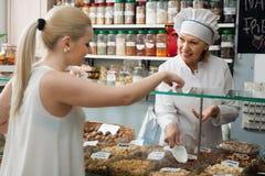 Smilingmature-Frau, die verschiedene Nüsse im lokalen Supermarkt kauft Stockfoto