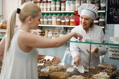 Smilingmature woman buying different nuts in local supermarket Stock Photo