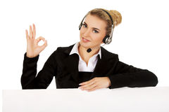 Smille call center woman holding empty banner and showing OK Royalty Free Stock Image