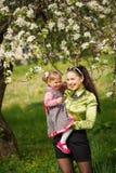 smilling在晴朗的公园的母亲和女儿 库存图片