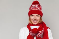 Smilling被编织的温暖的帽子和手套的冬天女孩在手上的拿着一个杯子 愉快的圣诞节妇女,隔绝在灰色背景 免版税库存照片