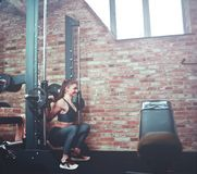 Smilling athletic woman exercising squatting with barbell. At smith machine against brick wall in gym royalty free stock images