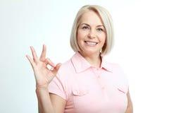 Smilling atrakcyjna w średnim wieku kobieta pokazuje aprobaty, ok odosobniony Obrazy Stock