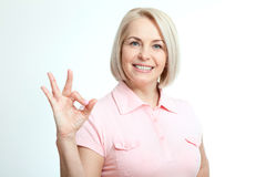 Smilling attractive middle aged woman showing thumbs up, okay. Isolated Stock Images