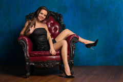 Smilling beautiful girl sitting in armchair and looking at the c Royalty Free Stock Image