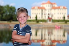 Smilling boy with arms akimbo by the chateau. Smilling boy blinking with arms akimbo by the chateau lake Stock Images