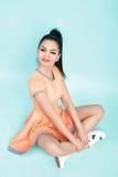 Smilling brunetki młoda kobieta w pomarańcze sukni obsiadaniu na podłoga na błękitnym tle Zdjęcia Stock