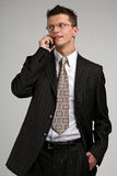 Smilling business man talking on a phone. Smilling business man talking on a mobile phone in a black suit Royalty Free Stock Photos