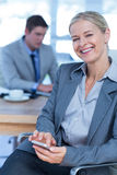Smilling businesswoman texting on her mobile phone Stock Photography