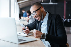 Smilling cheerful businessman texting message on the smartphone royalty free stock image