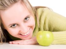 Smilling girl and green apple Stock Photos