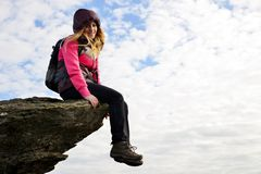 Smilling girl sitting on a rock. royalty free stock images