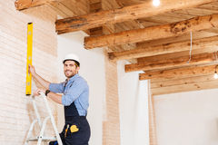 Smilling handsome builder using level and standing in the ladder Stock Photo