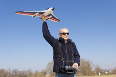 Smilling happy senior RC modeller launching plane Royalty Free Stock Images