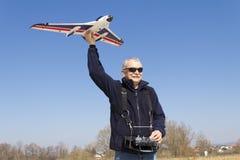 Smilling happy senior RC modeller launching plane Royalty Free Stock Images