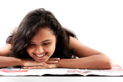 Smilling indian teen reading newspaper. Pretty indian woman reading the newspaper and smilling royalty free stock photography