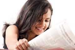 Smilling indian teen reading newspaper Stock Images