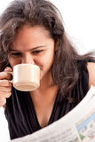 Smilling indian teen reading newspaper with coffee. Pretty indian woman reading the newspaper and smilling with coffee royalty free stock images
