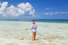 Smilling joyful happy little girl standing on a small stone in the ocean on sunny gorgeous day Royalty Free Stock Images