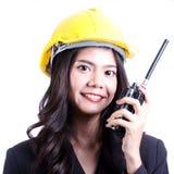 Smilling kvinnlig byggnadsarbetare som talar med en walkietalkie Arkivfoton
