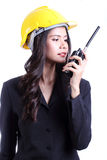 Smilling kvinnlig byggnadsarbetare som talar med en walkietalkie Arkivbilder