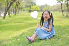 Smilling little Asian girl holding blank heart label lying on green grass at summer garden.  royalty free stock photography