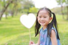 Smilling little Asian girl holding blank heart label lying on green grass at summer garden.  stock image