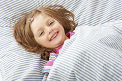 Smilling little girl in the bed Royalty Free Stock Images