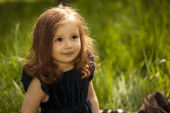 Smilling little girl on a grass Stock Photography