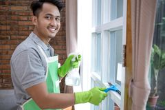 Man cleaning window. A smilling man cleaning window at home Royalty Free Stock Photography