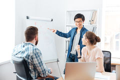 Smilling man making presentation to his colleagues and using flipchart Royalty Free Stock Images