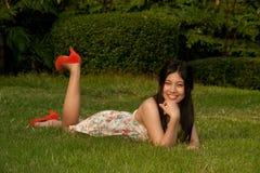 Smilling poserar den nätt asiatiska kvinnan av att ligga på en lawn i parkera royaltyfria foton
