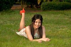 Smilling poserar den nätt asiatiska kvinnan av att ligga på en lawn i parkera royaltyfri fotografi