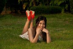 Smilling poserar den nätt asiatiska kvinnan av att ligga på en lawn i parkera fotografering för bildbyråer