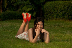 Smilling pretty Asian woman pose of lying on a lawn in the park Royalty Free Stock Photos