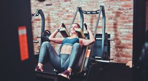 Smilling sportswoman doing squatting in training machine. Smilling sportswoman doing squatting in training machine at gym. Leg muscle training stock images