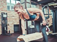 Smilling sporty woman pulling dumbbell on a fitness bench. In gym stock photo