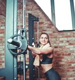 Smilling sporty woman with towel around her neck rests. Leaning on the barbell on background of brick wall with window in gym. Training break royalty free stock image
