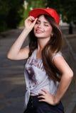 Smilling teen model. Beautiful smilling teen model on street. red cap, grey t-shirt, dark blue shorts Royalty Free Stock Photography