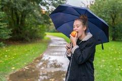 Smilling ung kvinna som äter det utomhus- äpplet arkivbild