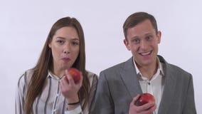 Smilling unga par, man och kvinna som äter röda äpplen Stående av mannen och kvinnan som isoleras på vit bakgrund lager videofilmer