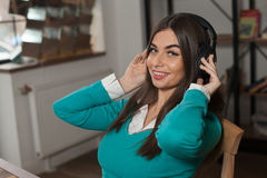 Smilling woman on chair with headphones Royalty Free Stock Image
