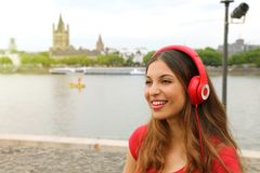 Smilling woman listening to music with european city landscape o royalty free stock image