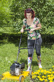 Smilling woman is mowing the grass Stock Photography